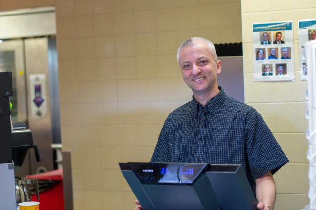 Smiling member of catering staff at the till