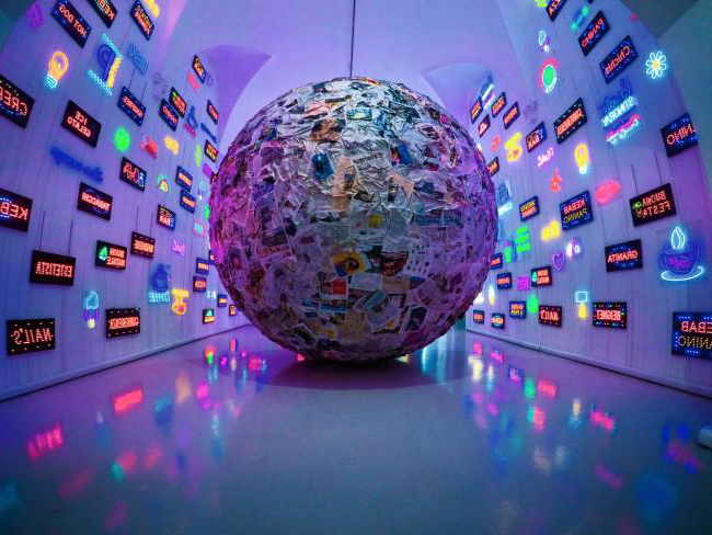 Image of a globe made from journal articles surrounded by neon signs